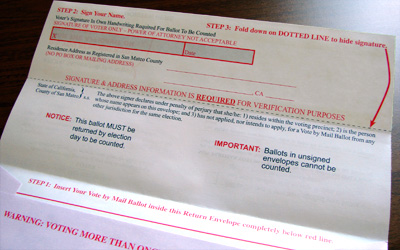 Vote-By-Mail envelope that has a lot of red writing and lines